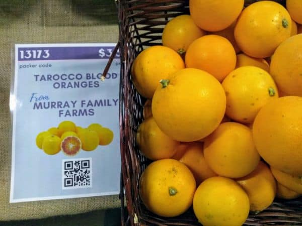 A basket of Tarocco blood oranges with a sign saying they are from Murray Family Farms.
