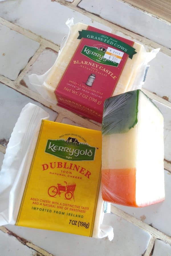 Kerrygold blarney castle cheese, Dubliner cheese, and a cheese with wax that represents the color of Ireland (green, white, and orange) sitting on a white tile countertop.