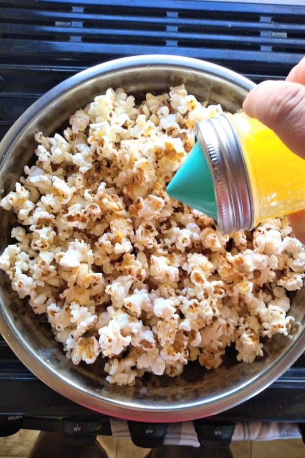 The Ergo Spout mini is attached to a mason jar full of butter and it's been poured onto a metal bowl full of popcorn.