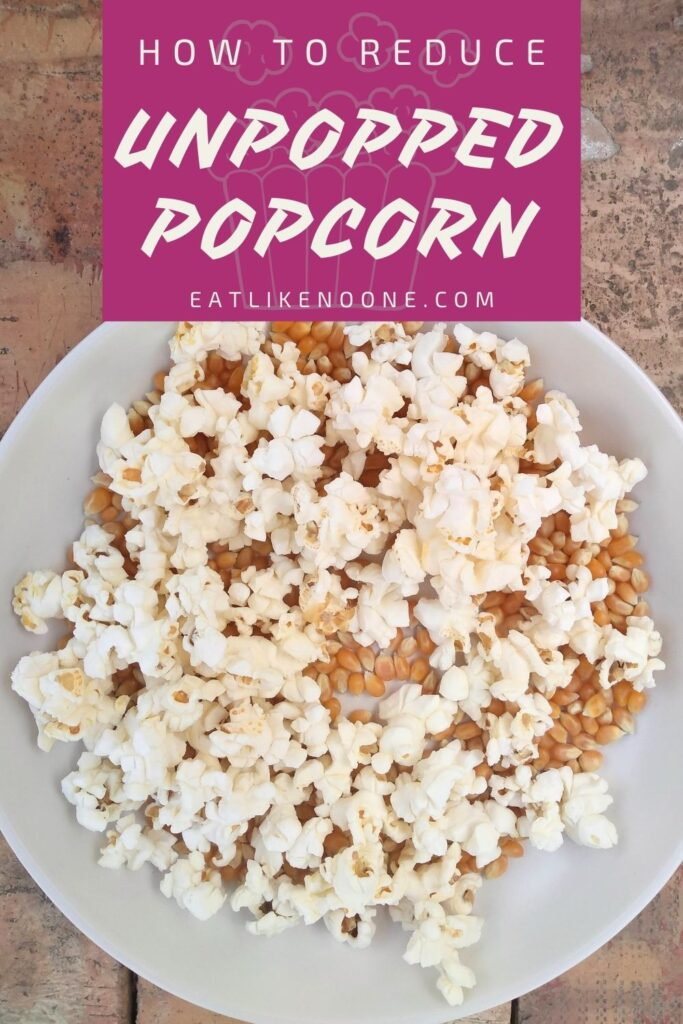 """A bowl of popcorn full of popped and unpopped kernels with the words """"How to Reduce Unpopped Popcorn"""" in a magenta box at the top of the photo."""