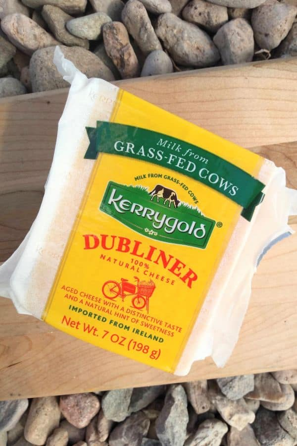 Kerrygold Dubliner cheese in it's package on top of a wood cutting board on top of some stones.