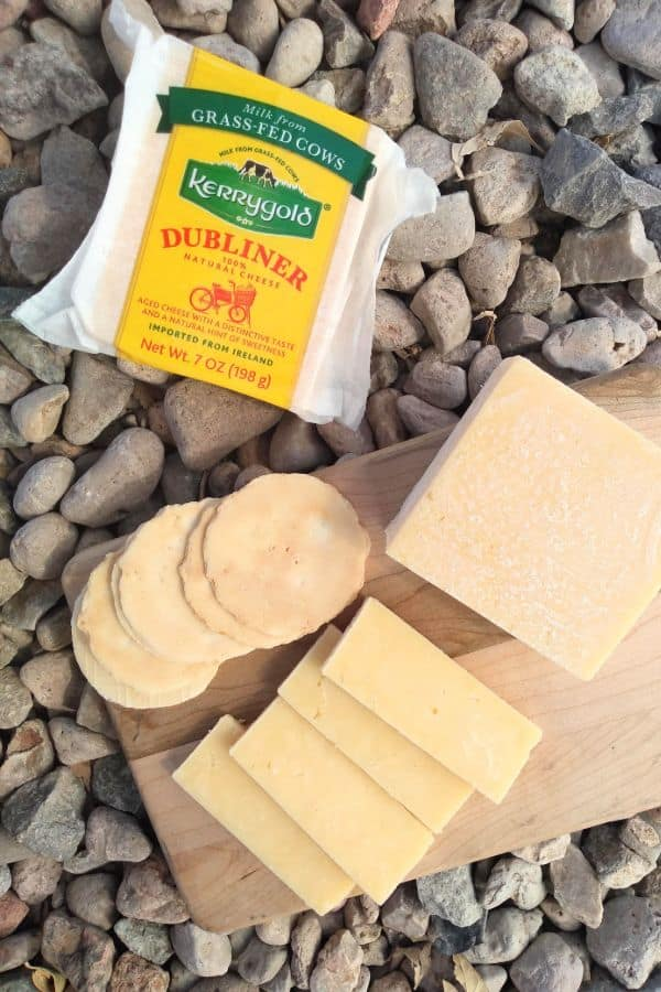 Kerrygold dubliner cheese sliced up on a wood cutting board with some crackers. A whole package is next to the board sitting on some rocks.