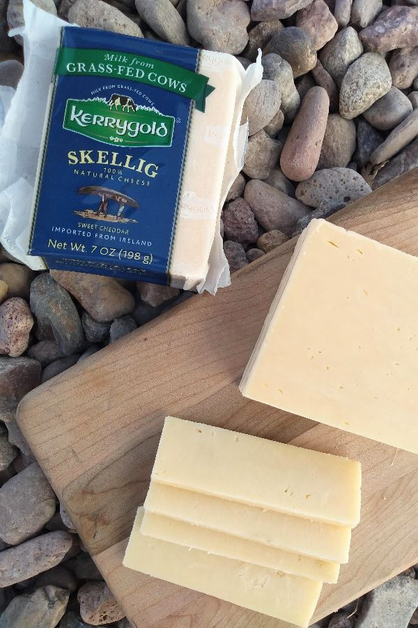 A block of Kerrygold Skellig Sweet Cheddar on a wood cutting board, cut into slices, on top of some stones.