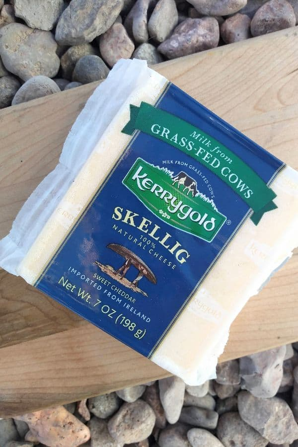 A picture of packaged Kerrygold Skellig sweet cheddar cheese on a wood cutting board on top of some rocks.