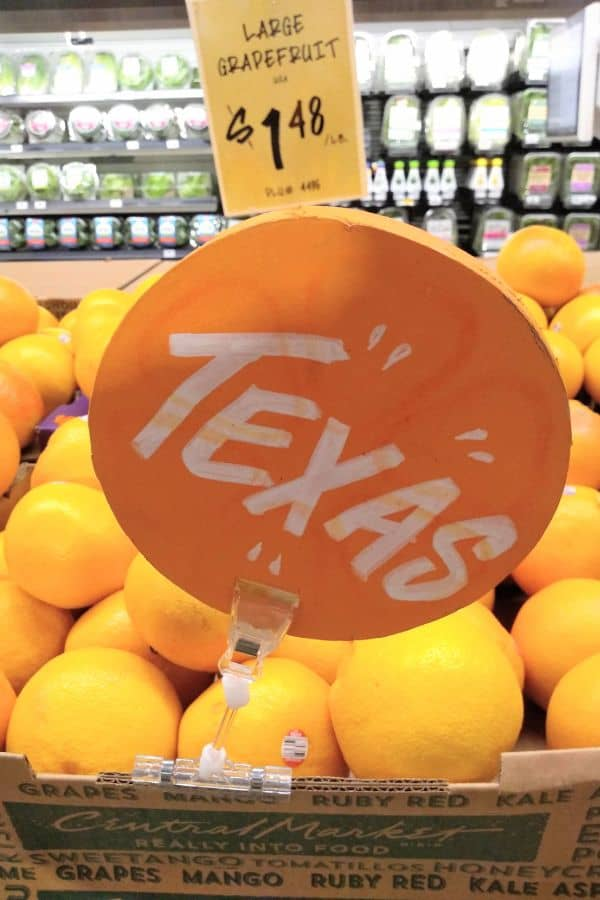"""A display of Texas grapefruit at a grocery store in Texas with a Texas sign and a sign in back that says """"large grapefruit $1.48/lb."""""""