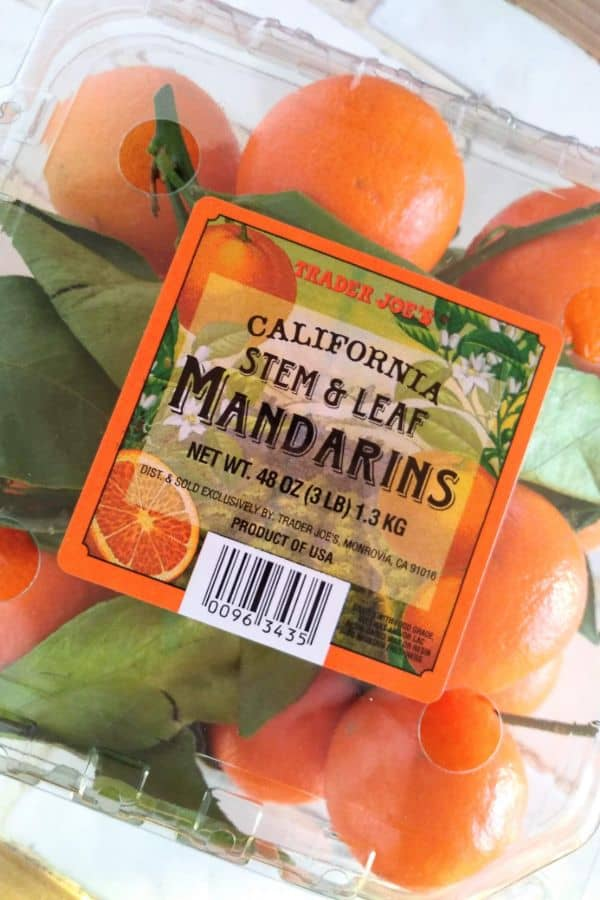 A plastic container of Trader Joe's California Stem and Leaf Mandarins sitting on a white counter.