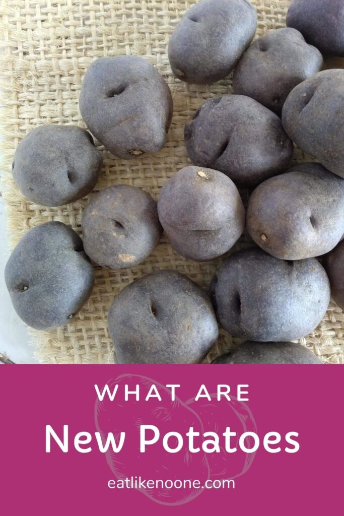 """Small purple potatoes on a burlap piece on a white countertop with the words """"What are New potatoes"""" underneath."""