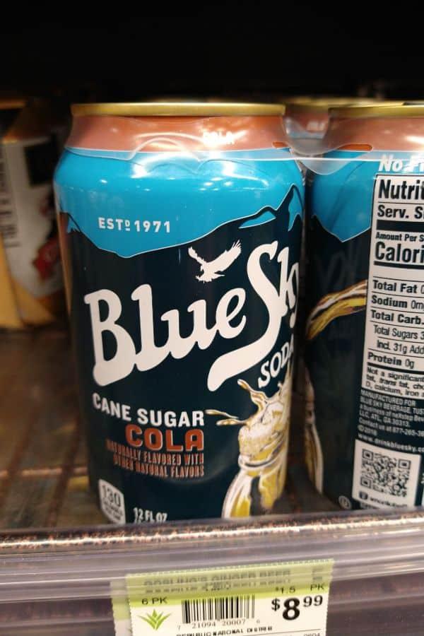 Blue Sky Cane Sugar Cola sitting on a store shelf.