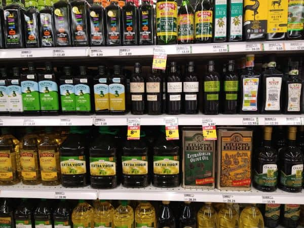 A multiple shelf display of different types of olive oil at the grocery store.