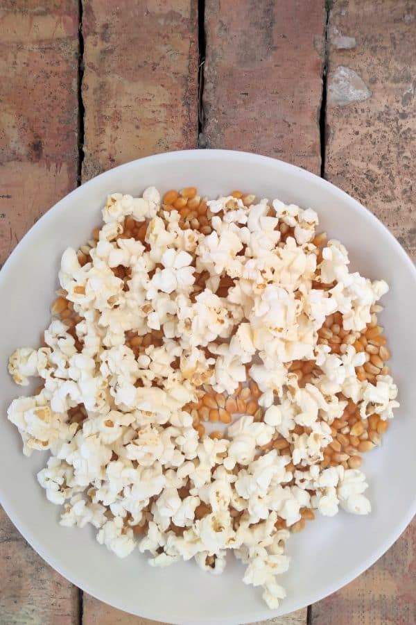 A bowl of popped popcorn and unpopped kernels sitting on a wood board.