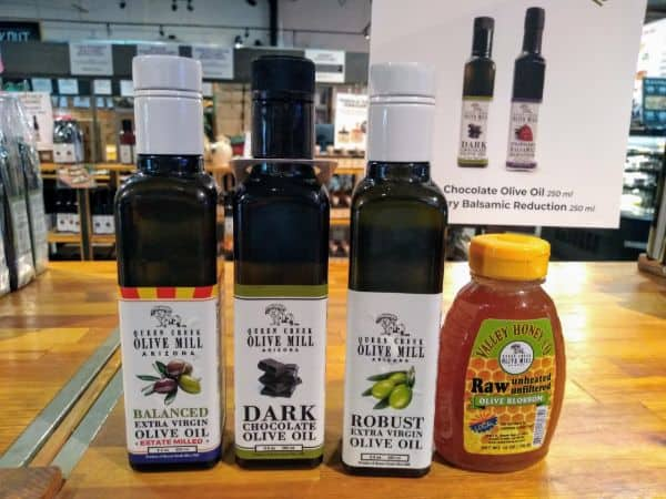 From left to right Queen Creek Olive MIll products Balanced Extra Virgin Olive Oil, Dark Chocolate Olive Oil, Robust Extra Virgin Olive Oil, Valley Honey Co. Raw Olive Blossom Honey