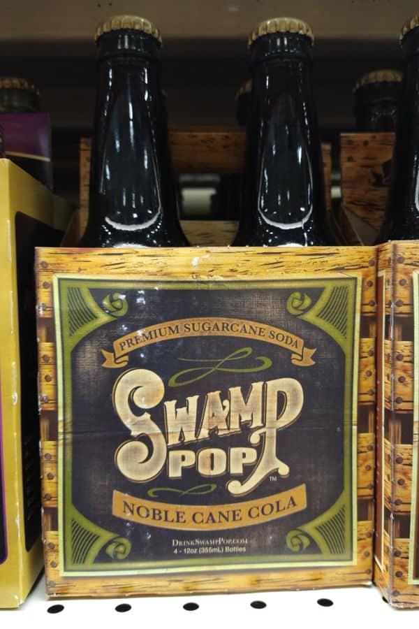 A 4-pack cardboard box of Premium Sugarcane Soda Swamp Pop Noble Cane Cola.