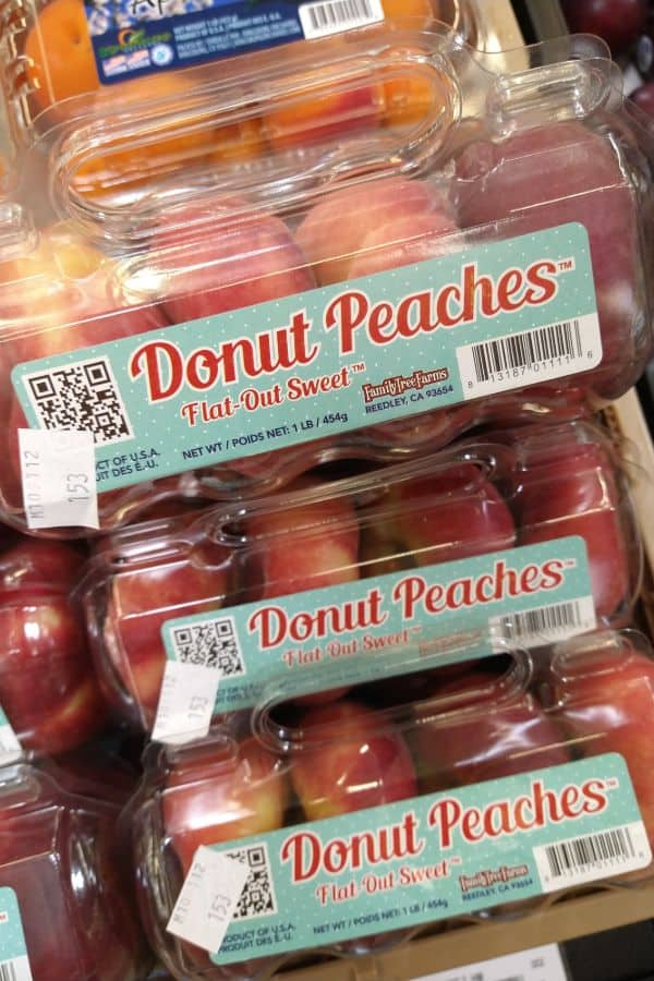 A plastic clamshell package of donut peaches that looks like a pack of donuts on display at the grocery store.
