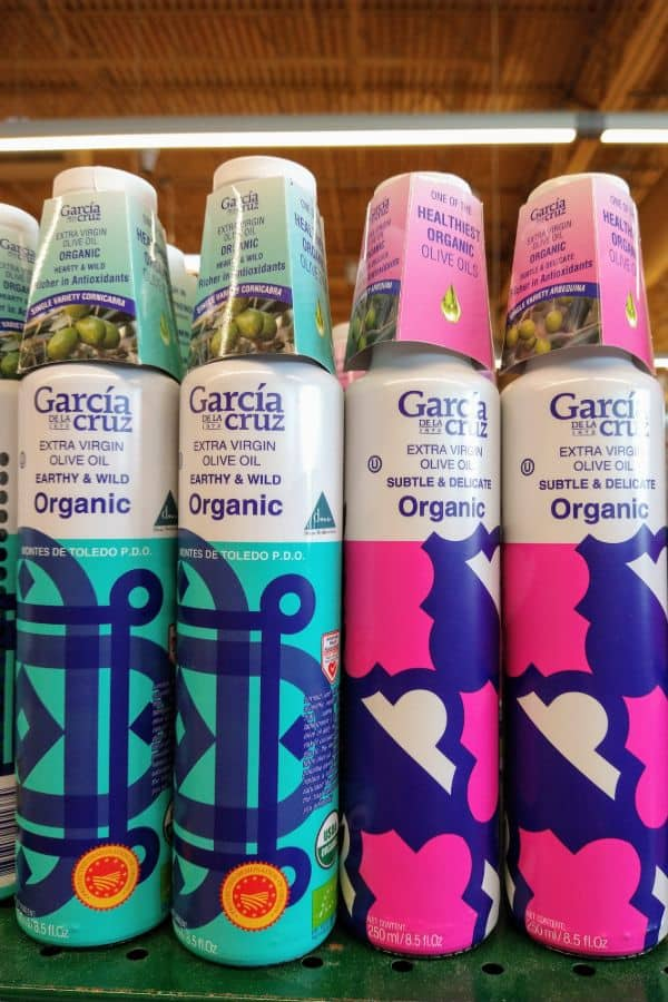 Garcia Cruz Extra Virgini Olive Oil in two types - earthy & wild and subtle & delicate on a shelf at a grocery store.