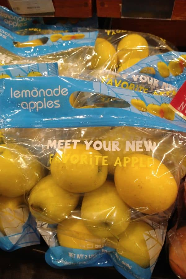 """See through 2 pounds bags of lemonade apples with a blue handle on top and the phrase """"meet your new favorite apple"""" on the bag."""