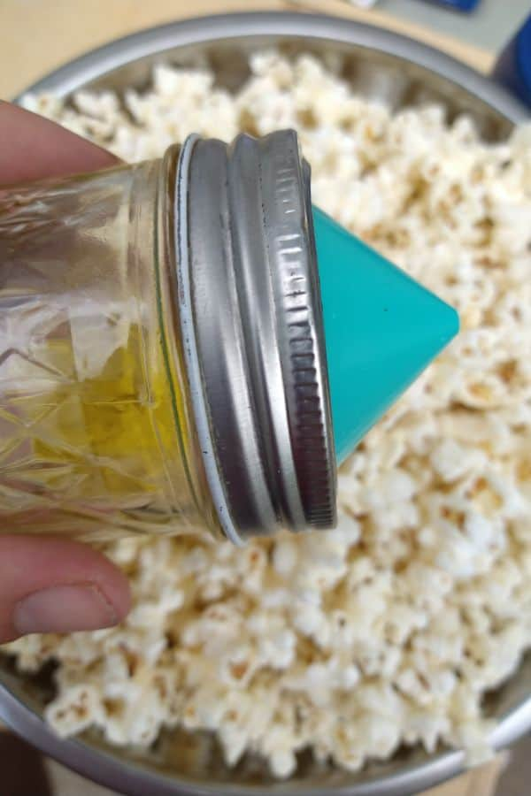 The Mini Ergo spout attached a small mason jar with olive oil in it, over top of a bowl of popcorn.