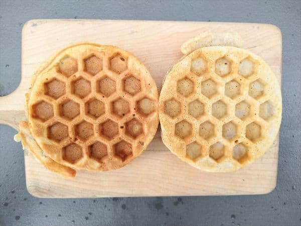 Two waffles sitting on a wood cutting board. The waffle on the left is more brown than the waffle on the right.