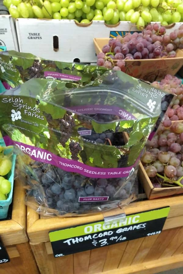 A bag of Organic Thomcord Seedless table grapes on display at a grocery store for $3.99/lb.