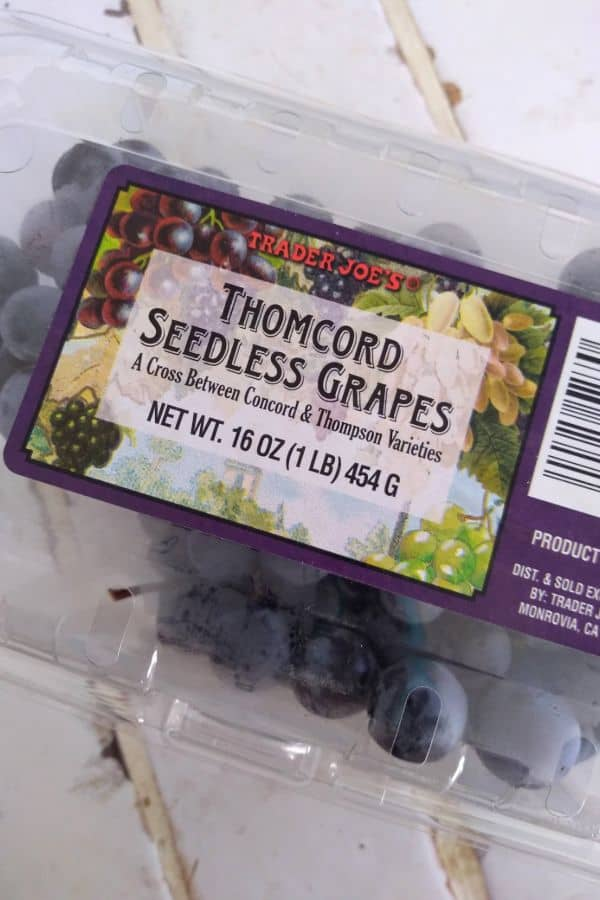 A package of Trader Joe's Thomcoard Seedless Grapes on a white tile countertop.