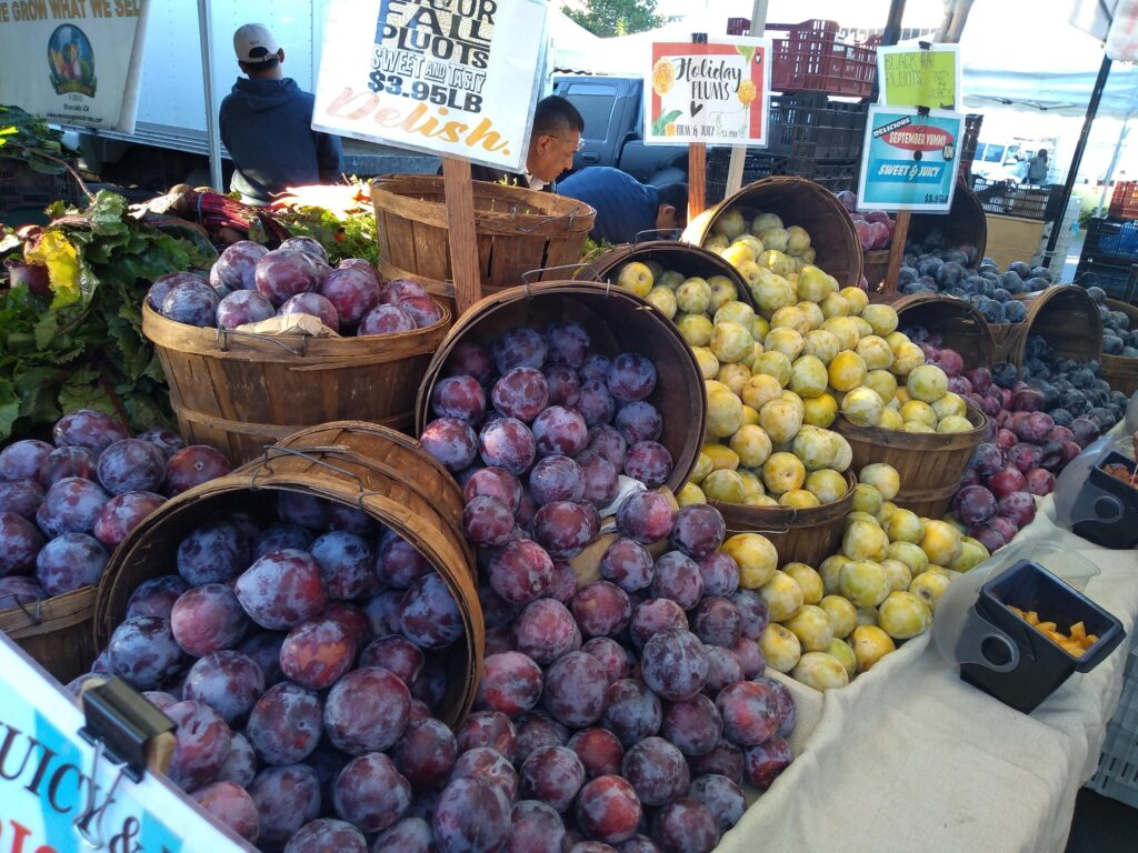A farmer's market display in California with half bushel wood baskets full of pluots and plums. Up front is the purple Flavor Fall Pluots selling for $3.95/lb.