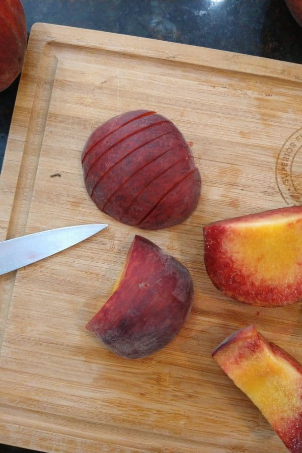 Slicing up peaches on top of a wood cutting board with a knife.