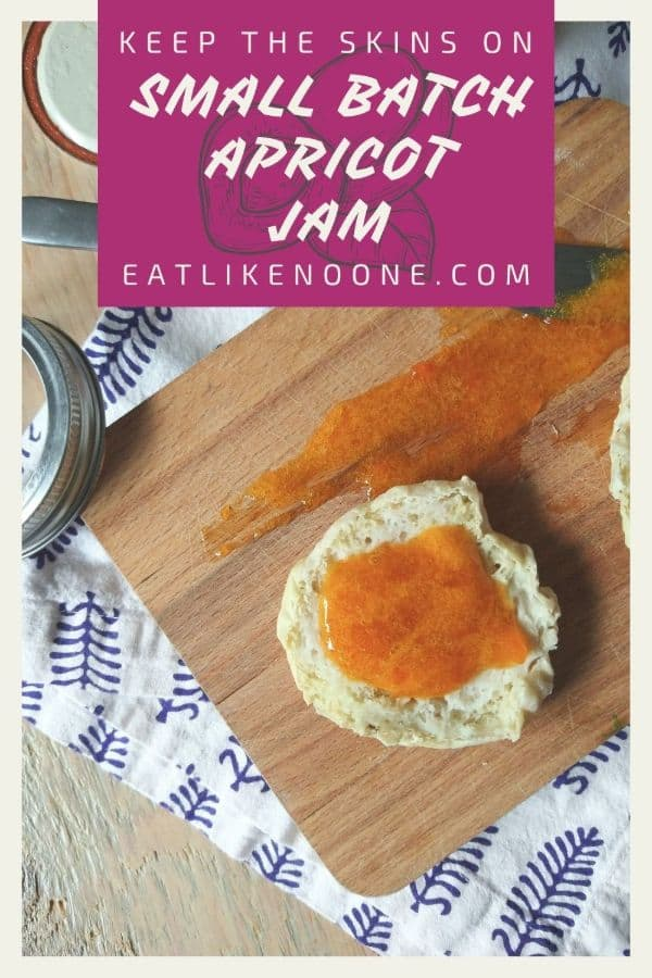 """An Enlighten muffin with apricot jam smeared onto it sitting on a wood cutting board with a white towel with a blue print. At the top in a maroon box it reads """"Keep the Skins On Small Batch Apricot Jam"""""""