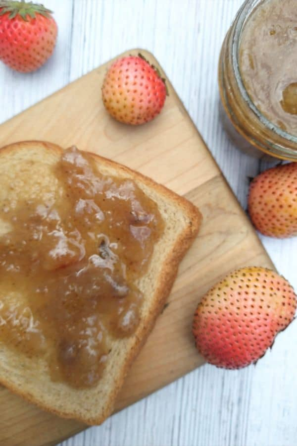 A slice of wheat bread on a wood cutting board. The bread has Rosé strawberry jam spread on it. A few strawberries are around the outside of the board and a small jar of brown colored jam is at the top, right corner.