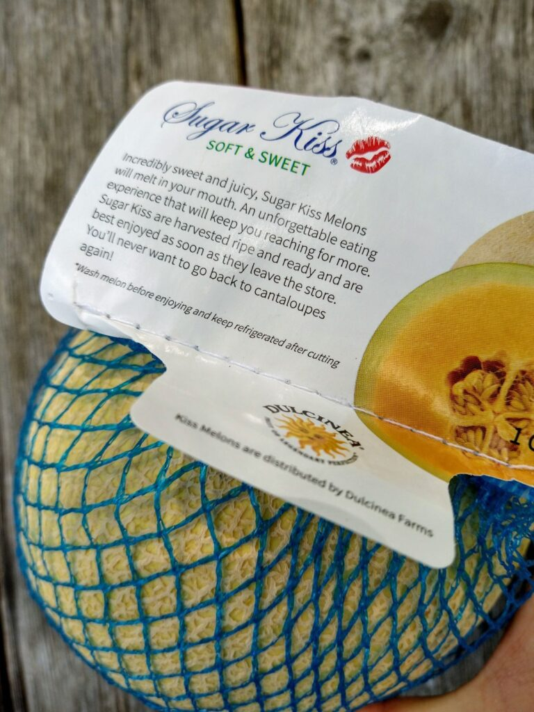 """The Sugar Kiss melon comes wrapped in blue netting with a label that reads """"Incredibly sweet and juicy, Sugar Kiss Melons will melt in your mouth. An unforgettable eating experience that will keep you reaching for more. Sugar Kiss are harvested ripe and ready and are best enjoyed as soon as they leave the store. You';; never want to go back to cantaloupes again!"""