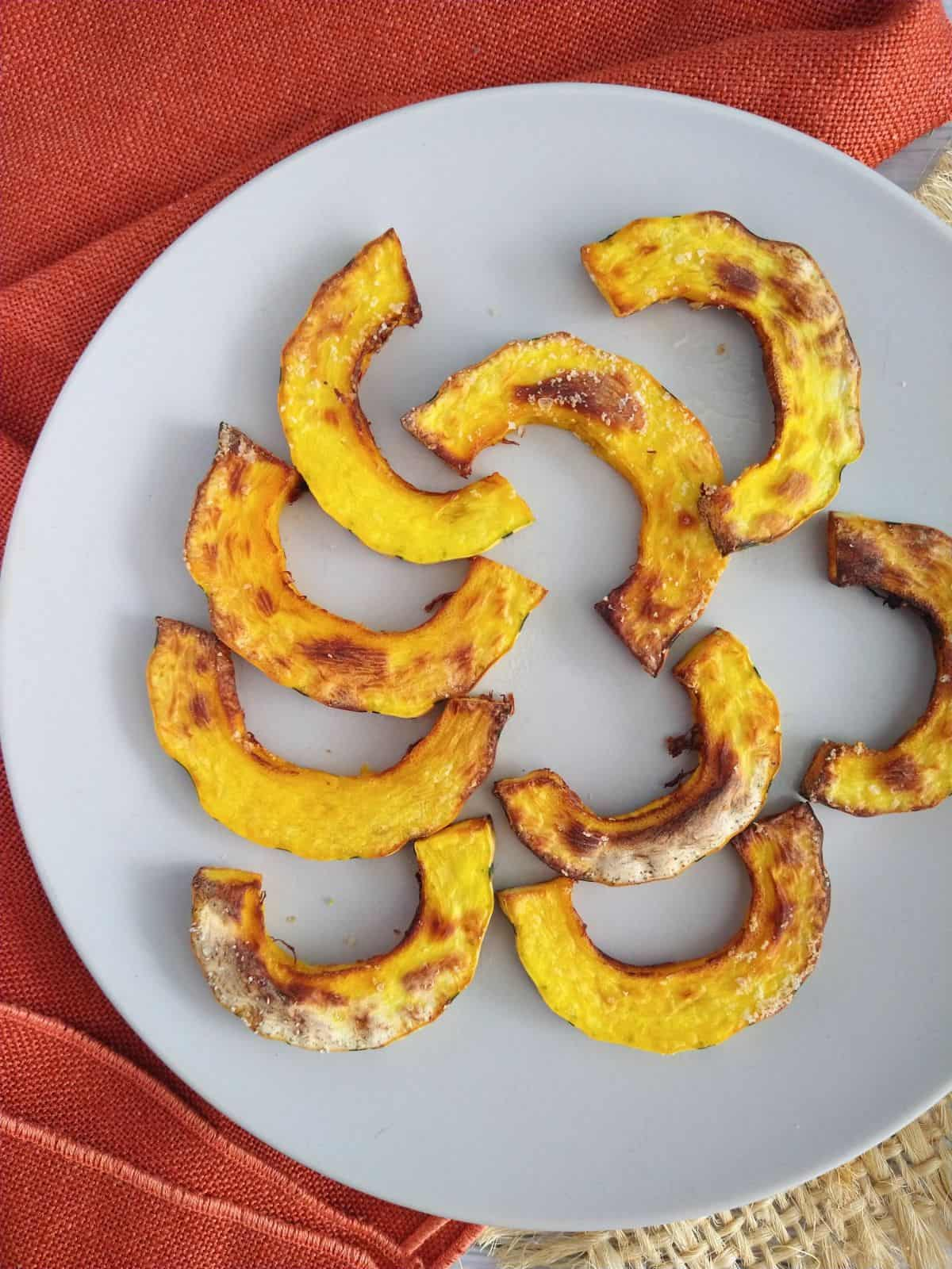 Air fryed Delicata squash cut into half moon shapes and cooked until starting to brown is sitting on a gray plate with a orange towel and piece of burlap underneath the plate.
