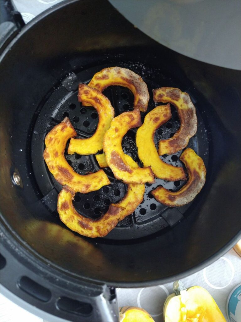 Delicata squash is finished cooking and it shown straight out of the air fryer in the basket.