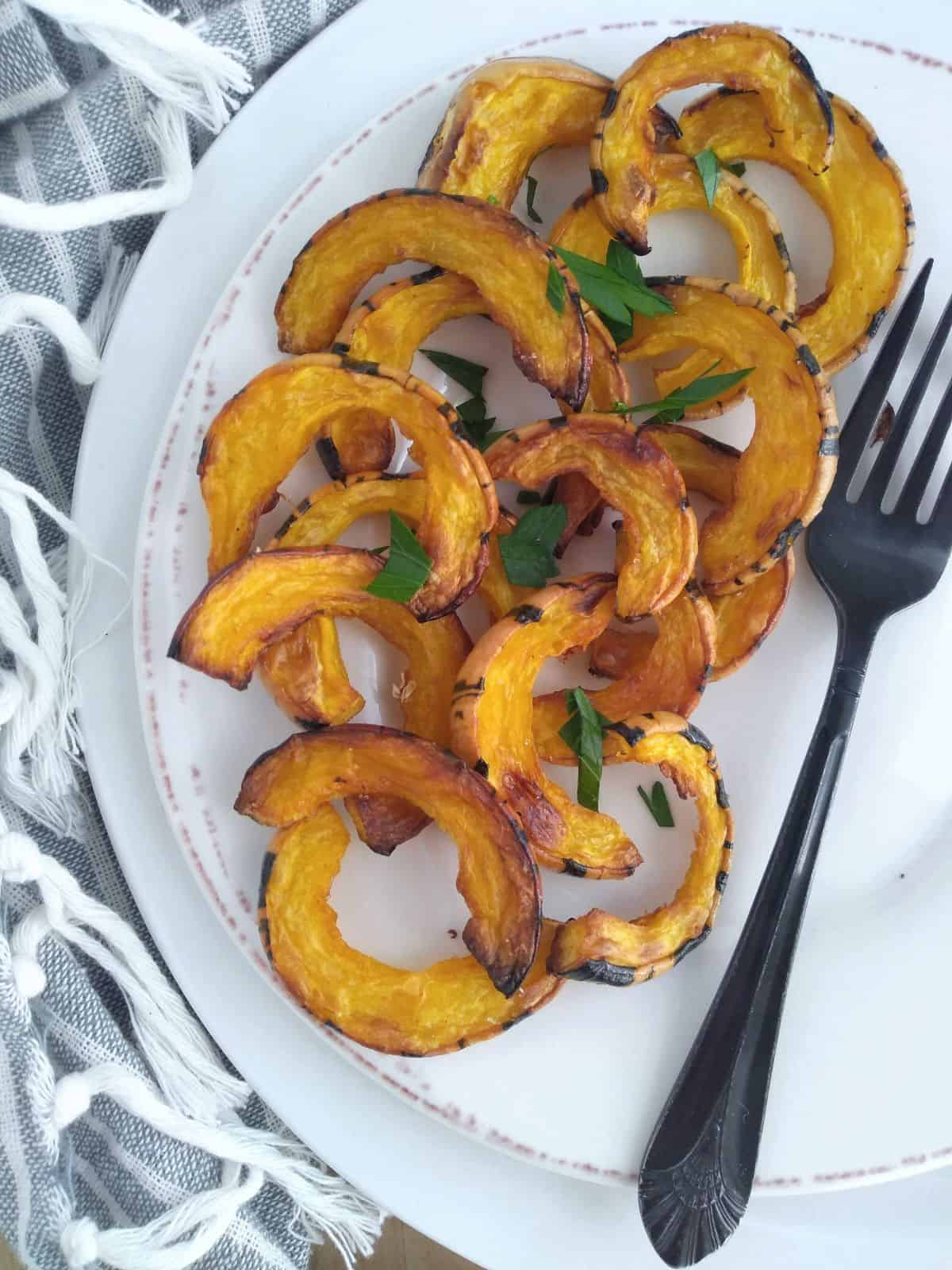 A plate of Roasted Delicata squash pieces with the skin on on top of a larger plate on top of a gray and white striped towel. A black fork is next to the squash.
