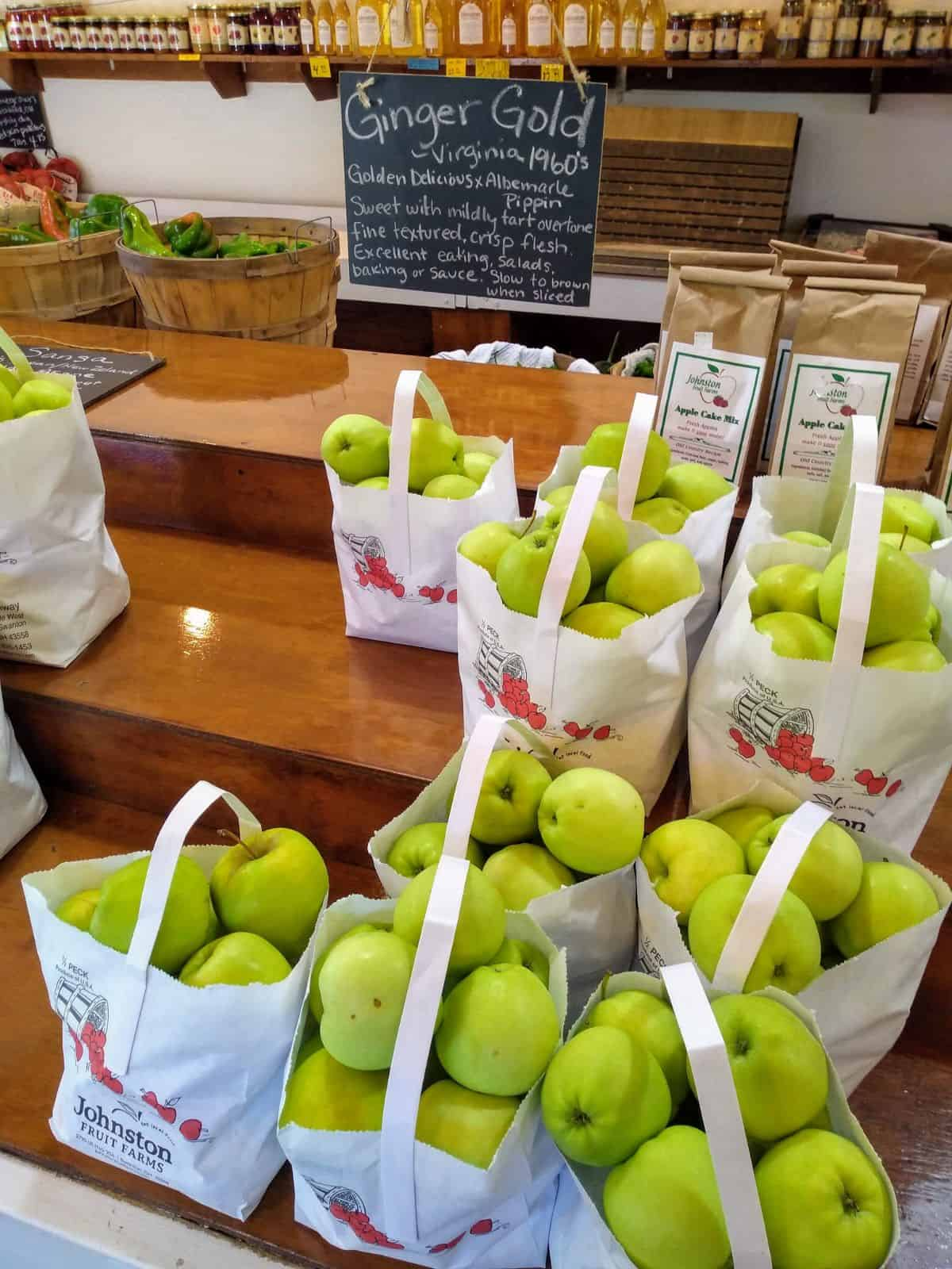 Bags of Ginger gold apples sit on a layered shelves at a farm market. The sign describes them as a cross between Golden Delicious and Albermale Pippin. Sweet with mildly tart overtone. Fine textured, crisp flesh. Excellent eating, salads, baking or sauce. Slow to brown when sliced.