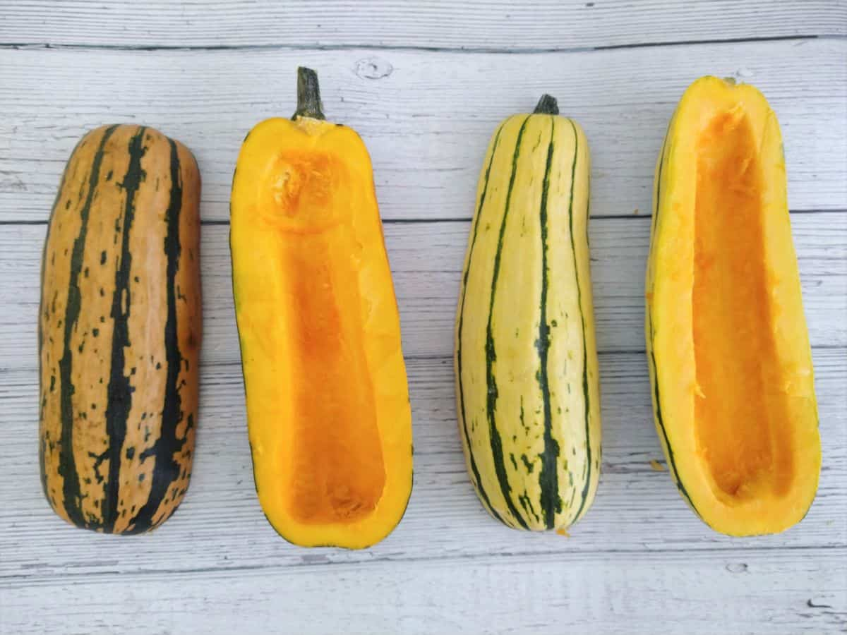 Two delicata squashes that have been sliced in half. Two of them are skin side up and two of them are skin side down. They are on a white wood grain surface.