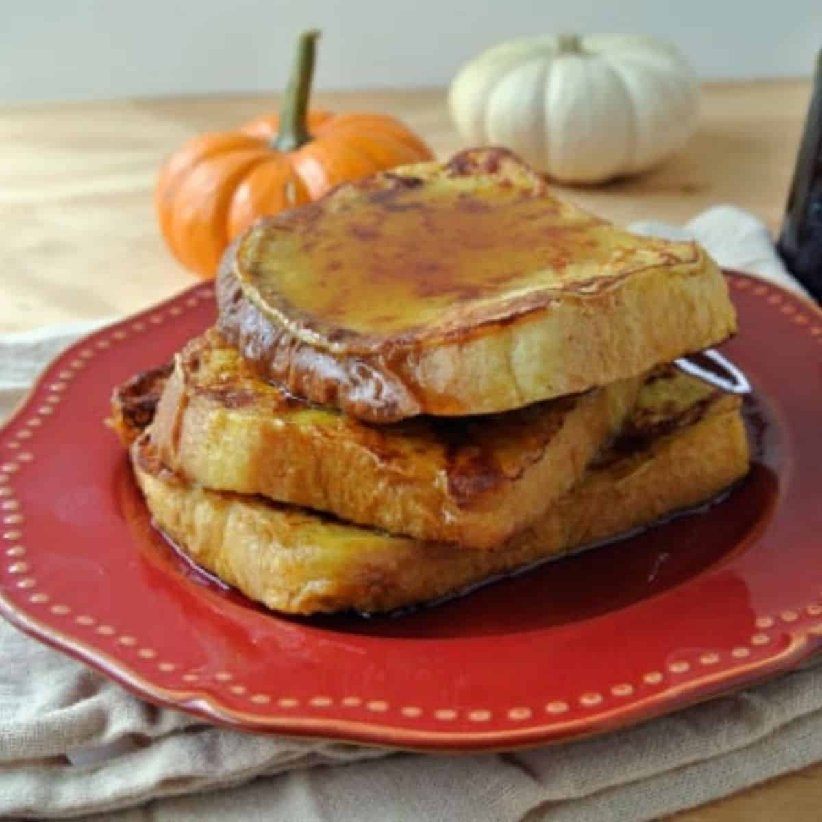 Three slices of pumpkin french toast sitting on a red plate. Maple syrup is on top of the slices with two mini pumpkins, one orange and one in the background