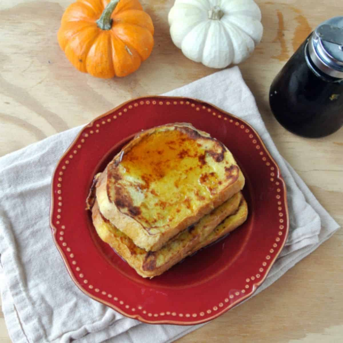 Three slices of pumpkin french toast on a red plate on top of a white towel. Nex to the plate is a container of maple syrup, 1 orange mini pumpkin, and 1 white mini pumpkin