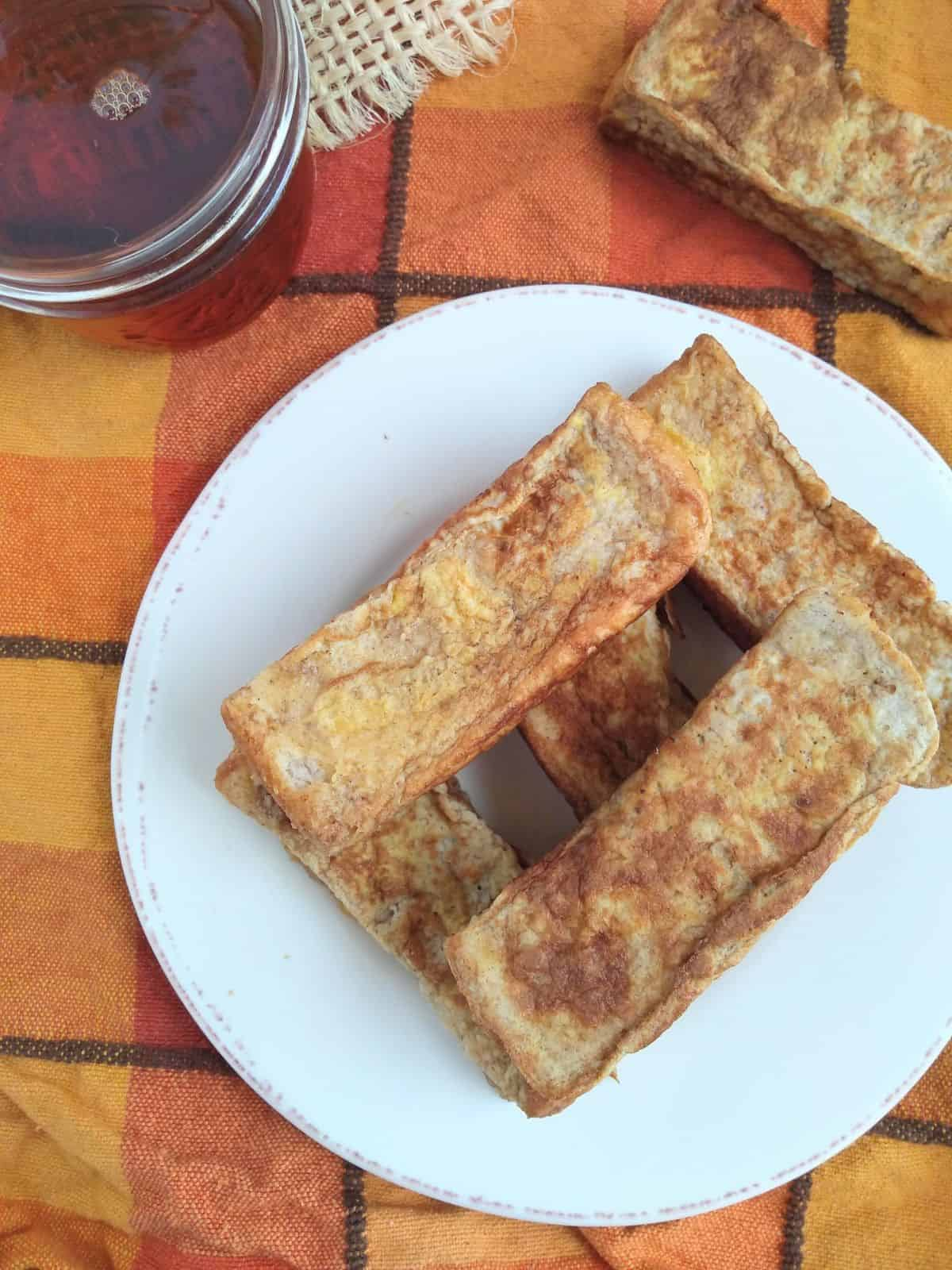 5 French toast sticks layered on a white plate with a orange-yellow-red plaid towel underneath. A jar of maple syrup next to it sitting on a piece of burlap