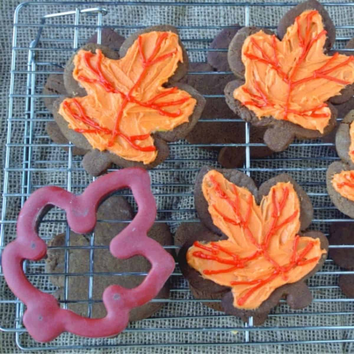 Four leaf shaped ginger cookies that have been frosting with pumpkin buttercream frosting that has been dyed orange and red are sitting on a wire drying rack. A leaf shaped cookie cutter is in the bottom corner.